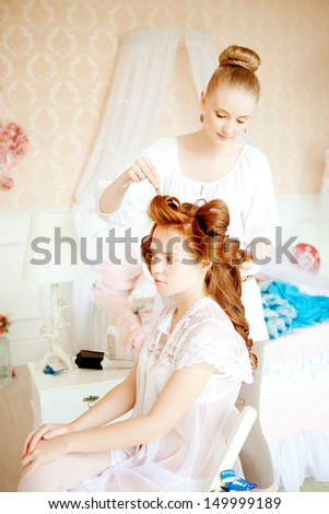 Hair stylist makes the bride on the wedding day - stock photo