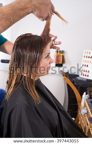 Hair stylist trimming freshly dyed hair - stock photo