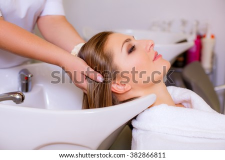 hair stylist washing woman hair in salon - stock photo