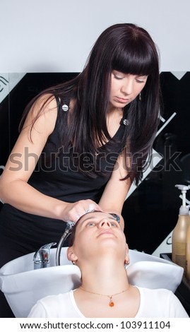 hair stylist washing woman head in hair salon