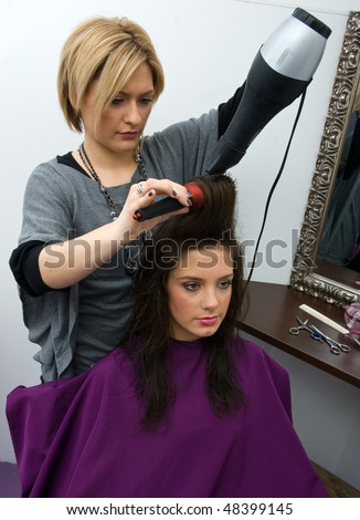 hair stylist with blower work on woman hair in salon - stock photo