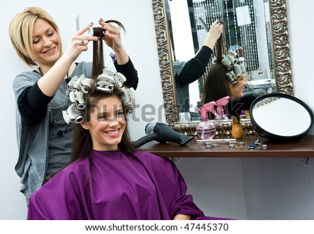 hair stylist work on happy woman hair in salon - stock photo