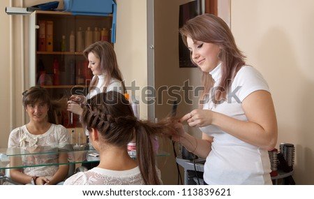 hair stylist works on woman hair in salon - stock photo