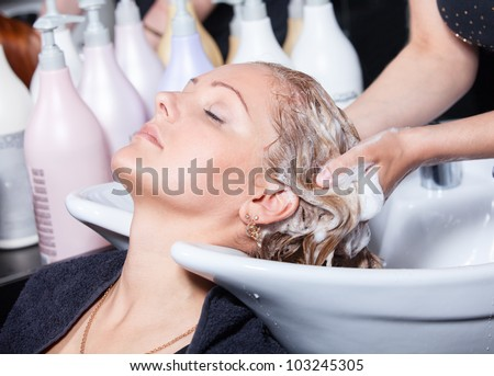 hair washing at a hairdressing salon, young caucasian girl - stock photo