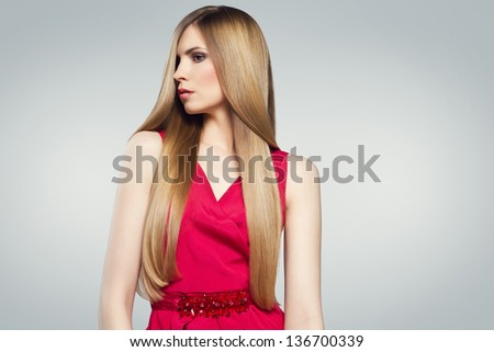 Hair. Young gorgeous caucasian blonde in red dress posing over grey background - stock photo
