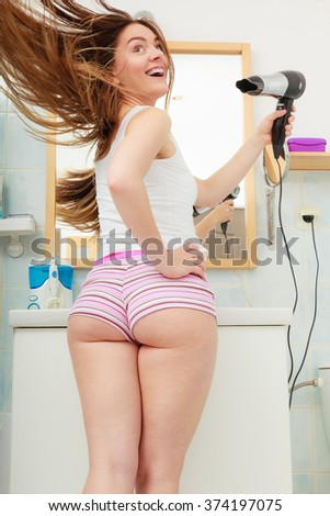 Haircare. Beautiful long haired woman drying hair in bathroom rear view