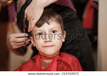 Haircut for little boy at professional barber - stock photo