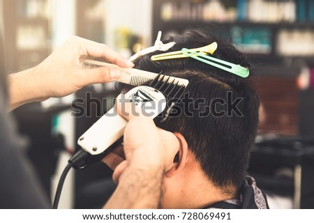 Haircut men Barbershop. Men's Hairdressers; barbers. Barber cuts the client machine for haircuts.hairdresser Asia