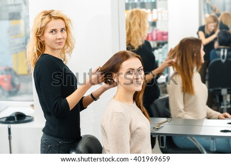 Haircut time. Cheerful young woman posing at the hair salon with her hairdresser looking to the camera smiling - stock photo