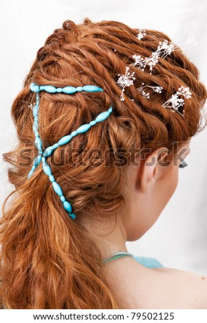 Hairdress of the red-haired girl with blue ornaments