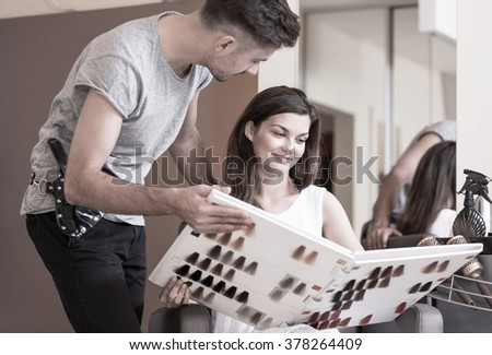 Hairdresser advising his client of a hair dye colour - stock photo