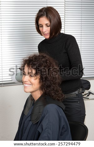Hairdresser blow drying woman's hair after giving a new haircut at parlor - stock photo