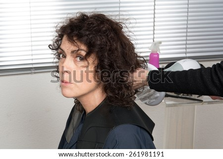 Hairdresser blow drying woman's hair after giving a new haircut at parlor