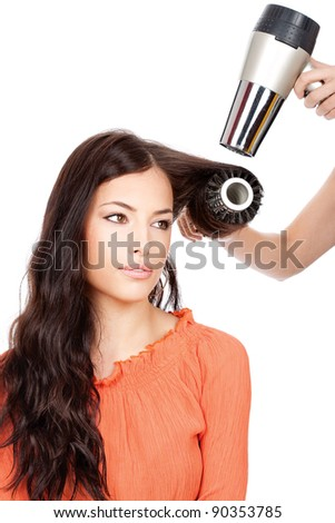 hairdresser combing and dry the hair of a woman, isolated on white background