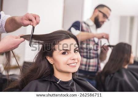 Hairdresser combing hair of female client in hairdressing salon.