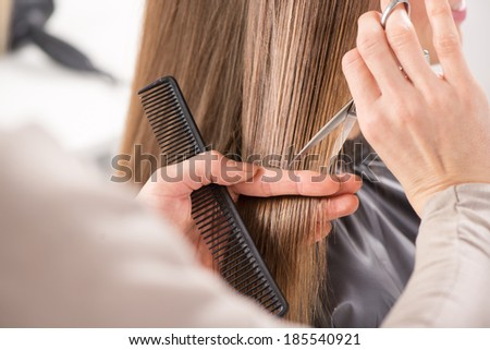 Hairdresser cut hair of a woman. Close-up.