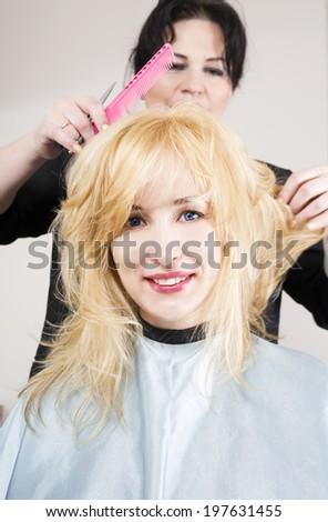 Hairdresser cuts (trims) blond long hair - stock photo