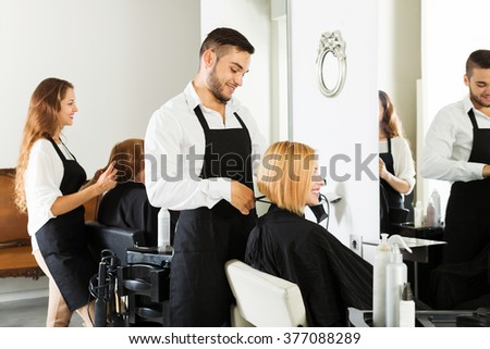Hairdresser cuts young girl's hair in the hair salon - stock photo