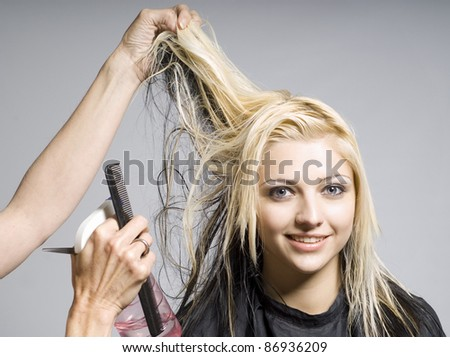 Hairdresser cutting hair of woman of smiling girl - stock photo