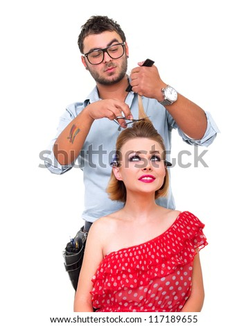 Hairdresser cutting woman's hair, isolated on white - stock photo