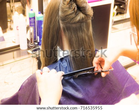 Hairdresser doing haircut in hairdressing salon. Hairdresser cutting hair. Beauty industry.