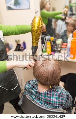 Hairdresser dries the hair dryer blond  hair
