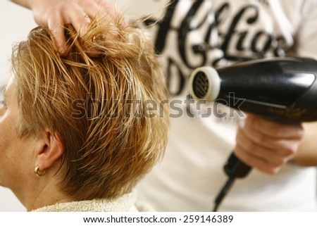 Hairdresser Drying the woman hair in salon  - stock photo