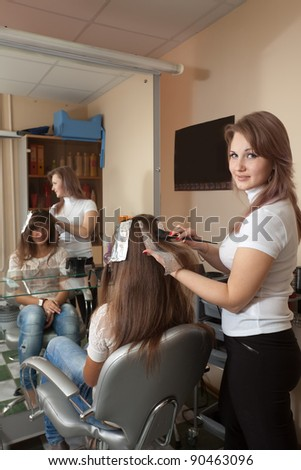 Hairdresser dye his hair long-haired girl