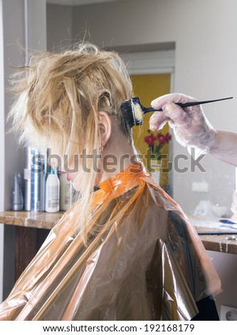 Hairdresser dyes long blond hair - stock photo