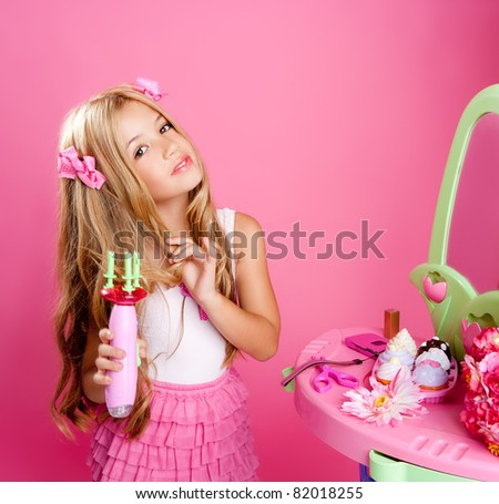 hairdresser fashion doll girl with hair curler in pink vanity - stock photo