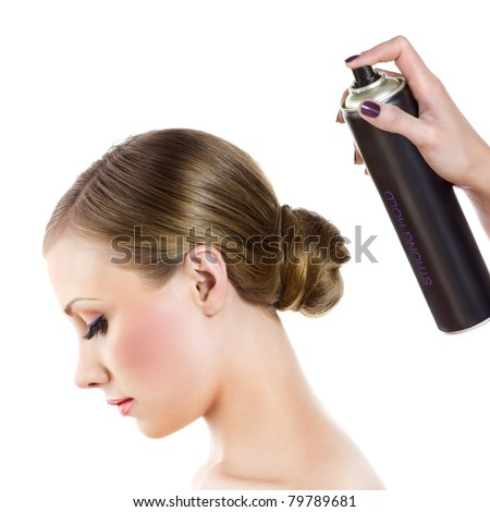 Hairdresser fixing woman hair with hairspray - stock photo