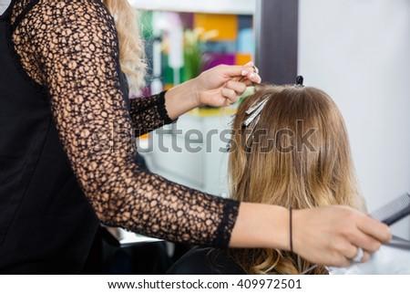 Hairdresser Highlighting Customer's Hair In Salon - stock photo
