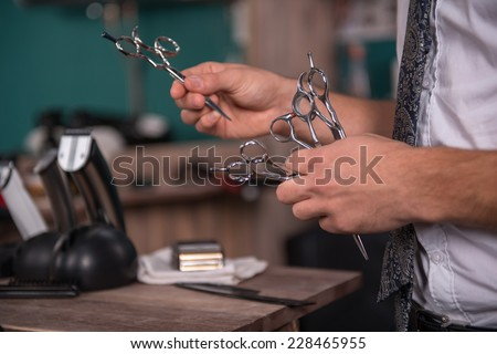 hairdresser  holding many pairs of scissors in in  professional  hairdressing salon   with selective focus - stock photo