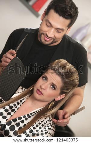 Hairdresser holding mirror for annoyed European customer - stock photo