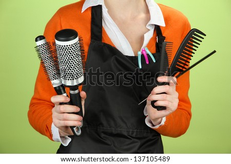 Hairdresser in uniform with working tools, on color background