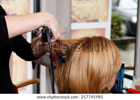 hairdresser is brushing hair close up  - stock photo