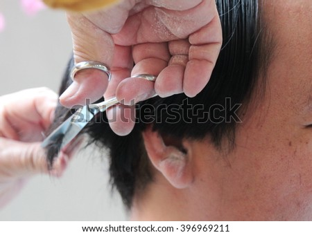 Hairdresser is cutting black hair with scissors