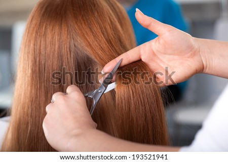 Hairdresser is cutting customer hair with scissors - stock photo