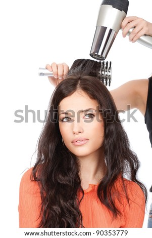 hairdresser is drain a woman's long black hair, isolated on white - stock photo