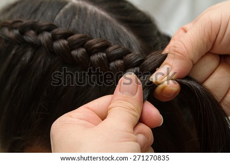 Hairdresser make braids in beauty salon - stock photo