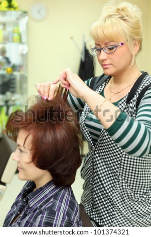 Hairdresser makes hair styling for woman by rake-comb in beauty salon - stock photo