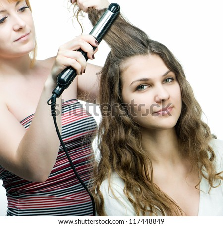 Hairdresser makes hairstyle for young attractive girl - stock photo
