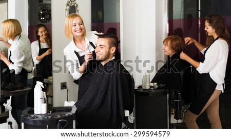 Hairdresser makes the cut for man in the hairdressing salon - stock photo