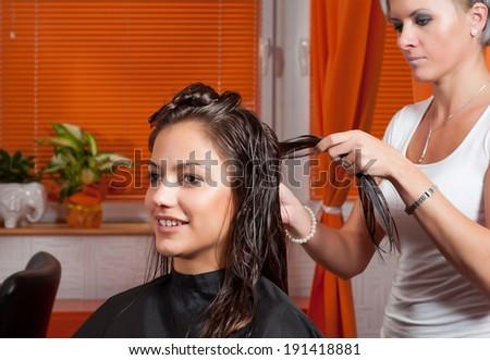 Hairdresser making hair of beautiful smiling teenage girl. - stock photo