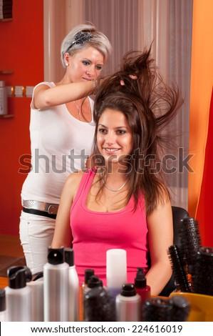 Hairdresser making hair of beautiful smiling teenage girl in hair salon. - stock photo