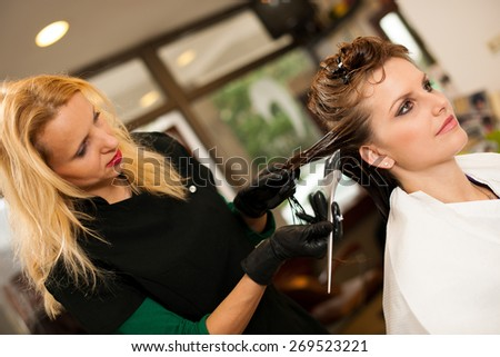 Hairdresser making hair treatment to a customer in salon - stock photo