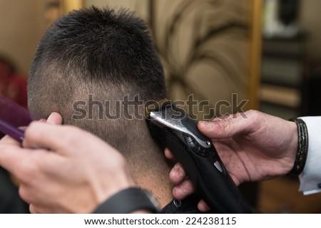 Hairdresser Making Haircut To Young Man - Handsome Young Hairdresser Giving A New Haircut To Male Customer At Parlor - stock photo