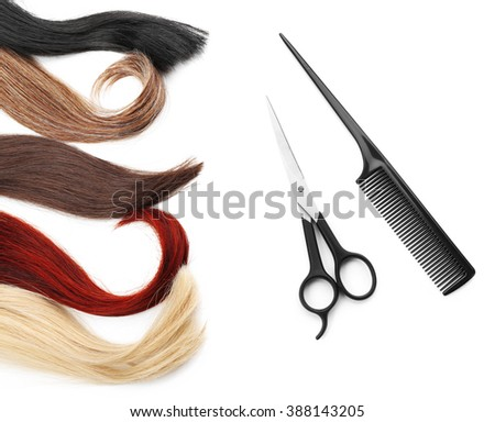 Hairdresser's scissors with comb and varicolored strands of hair, isolated on white