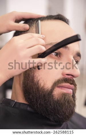 Hairdresser shaving an old-fashioned razor of  client in professional hairdressing salon. - stock photo