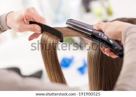 Hairdresser straightening long brown hair with hair irons. - stock photo